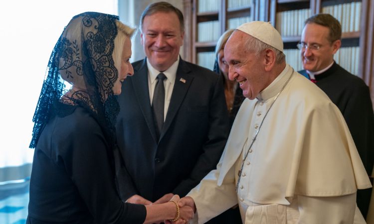 Ambassador Gingrich smiles and shakes hands with Pope Francis. Secretary Pompeo and two other people are also smiling in the background.
