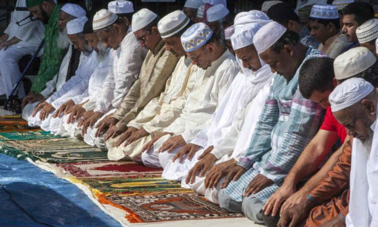Many men are kneeling with their heads bowed and their hands on their laps. Many of them men are wearing head coverings.
