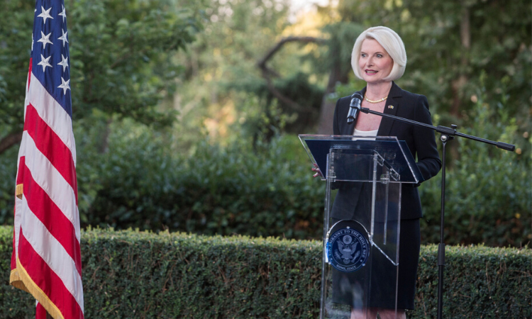 Ambassador Gingrich giving a speech at a lectern outside