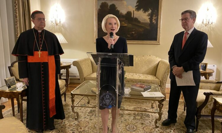 Ambassador Gingrich giving a speech on a lectern, with two other individuals standing next to her.