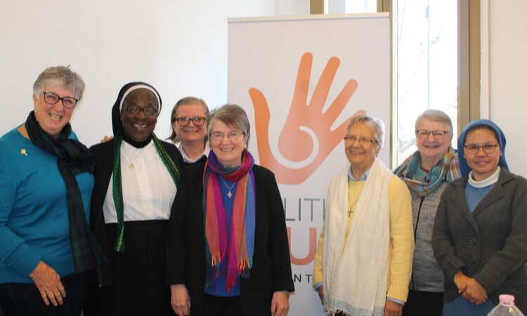 Seven women, including two nuns, stand together and smile at the camera. Behind them, there is a banner with a cartoon hand with the words Talitha Kum.