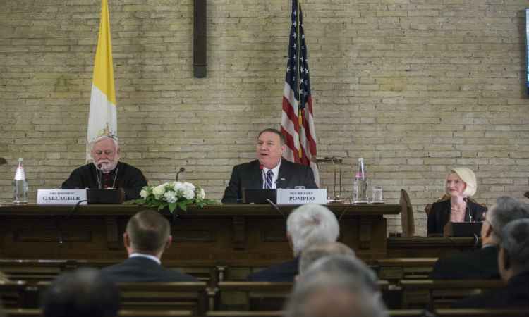 Archbishop Gallagher, Secretary Pompeo, and Ambassador Gingrich are seated behind wooden desks. The flags of the United States and the Holy See are behind them. The heads of some of the audience members appear in the foreground.
