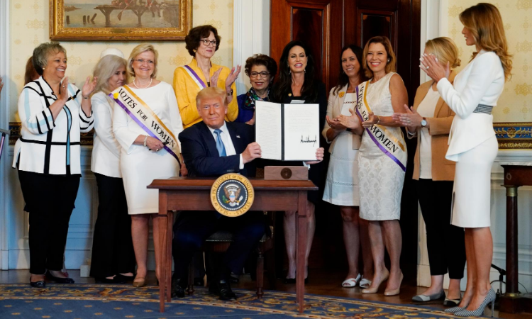 President Donald Trump holds a signed proclamation recognizing the 100th anniversary of the ratification of the 19th Amendment with first lady Melania Trump, far right, Tuesday, Aug. 18, 2020, in the Blue Room of the White House in Washington. (AP Photo/Patrick Semansky)