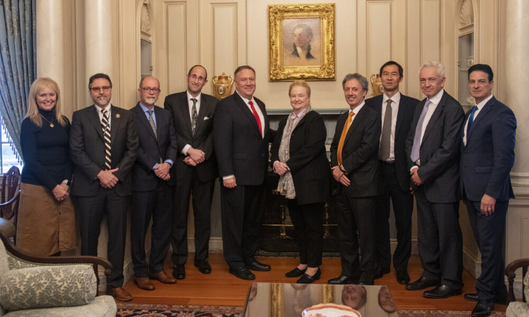 Ten people, including Secretary Pompeo stand together and pose for a photo. This event took place indoors.