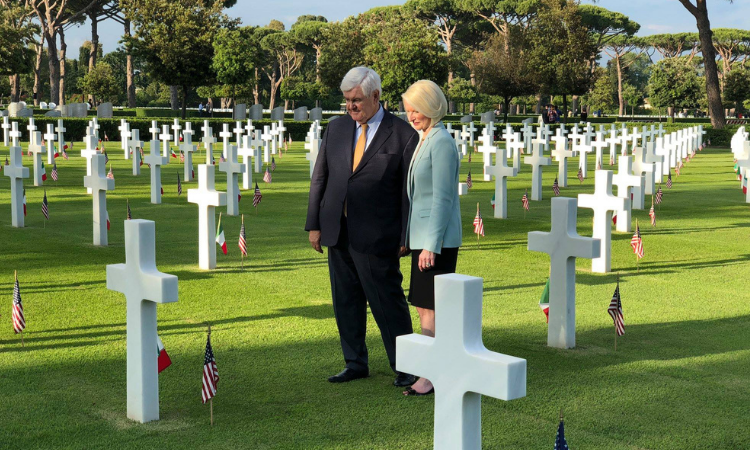 Ambassdor Gingrich standing over graves on Veterans day